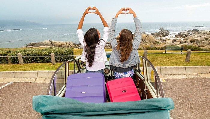 deux femmes formant un coeur avec leurs mains près de la valise american tourister bon air spinner