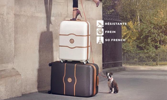 Femme debout sur la valise delsey chatelet hard+ afin de prouver sa solidité
