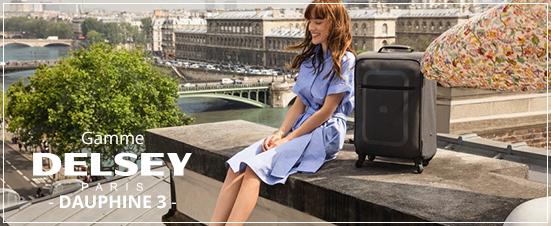 femme souriante sur un rebord avec la valise delsey dauphine 3