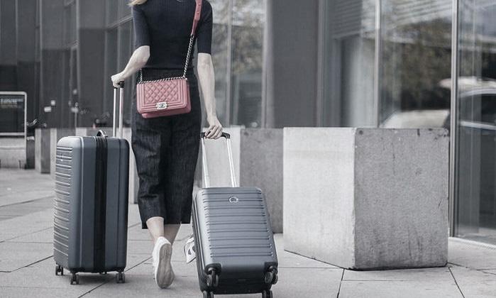 Femme se promenant avec une valise segur de la marque delsey