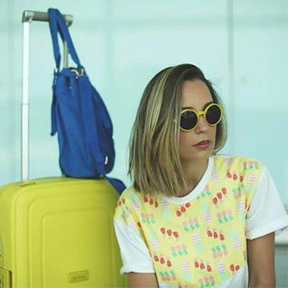 femmme a lunette jaune avec une valise samsonite s'cure jaune