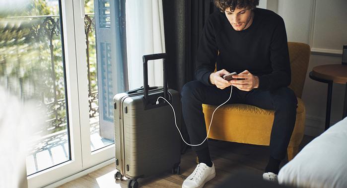 homme tenant un iphone qui charge sur sa valise horizn studios